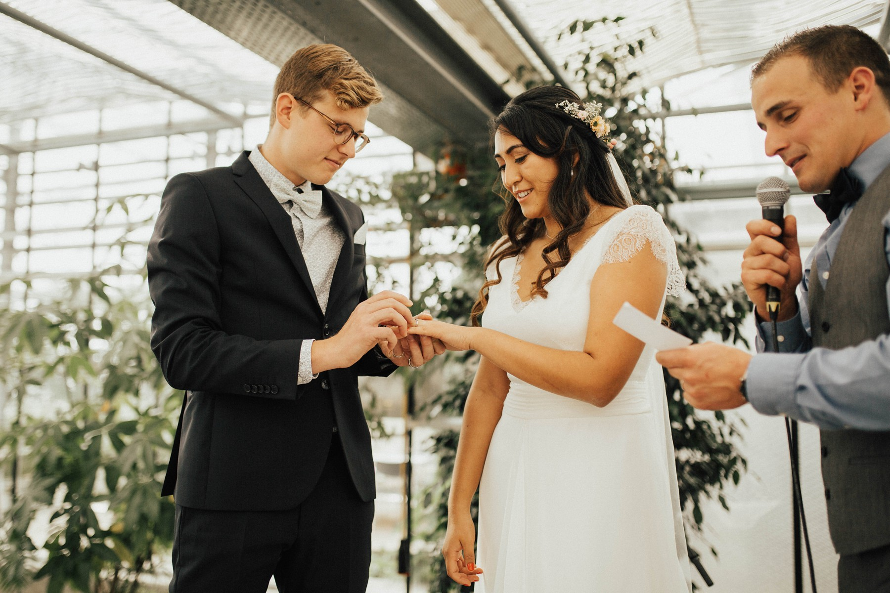 groom putting ring on in a greenhouse