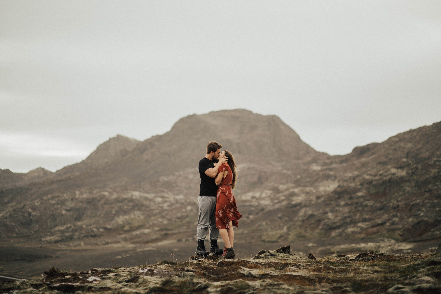 couple standing in epic landscape on a rock