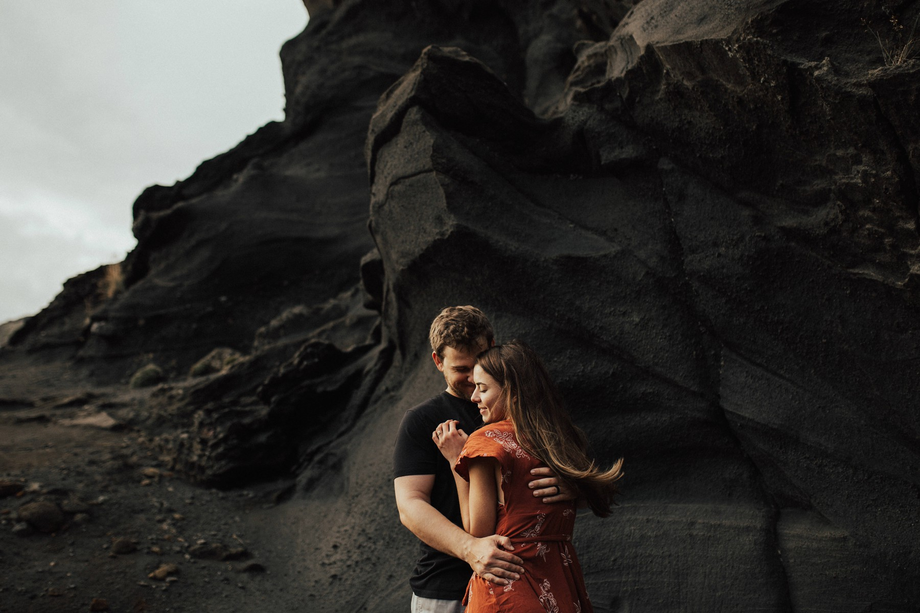 hugging couple in front of black rocks in iceland