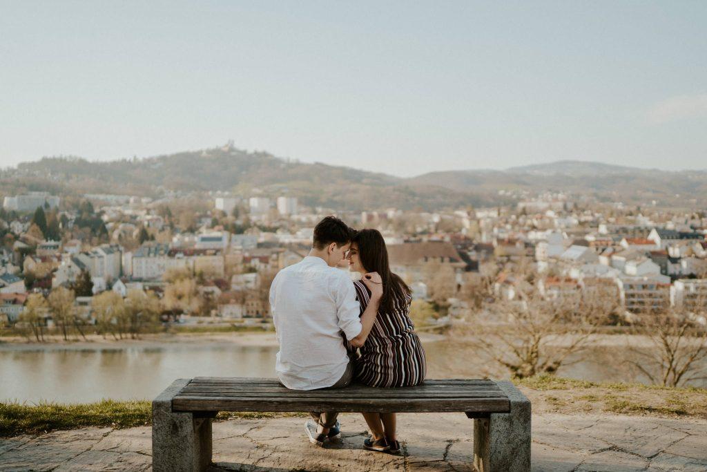 Paar sitzt auf Bank am Schlossberg Linz mit Pöstlingberg im Hintergrund
